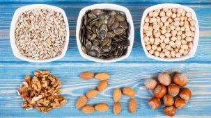 Aliments riches en zinc : il y a de la viande, du saumon, des crevettes, des légumineuses, du fromage, des noix et des épinards sur une table en bois.
